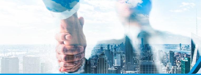 Imagen de manos estrechándose sobre una ciudad para cerrar un trato de venta
